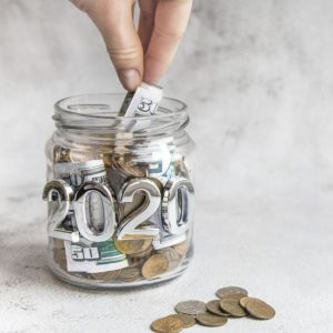 Budget 2020. Glass jar with money, coins and notes, savings, loans and mortgages
