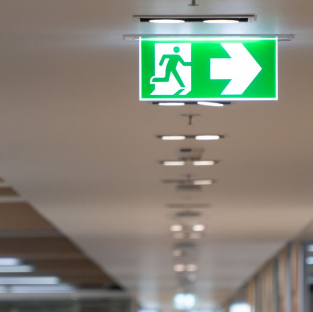 Green fire escape sign hang on the ceiling in the office