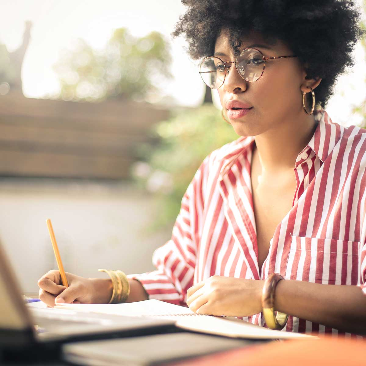 woman studying laptop screen with pencil in hand and notebook in front of her; woman working on a project