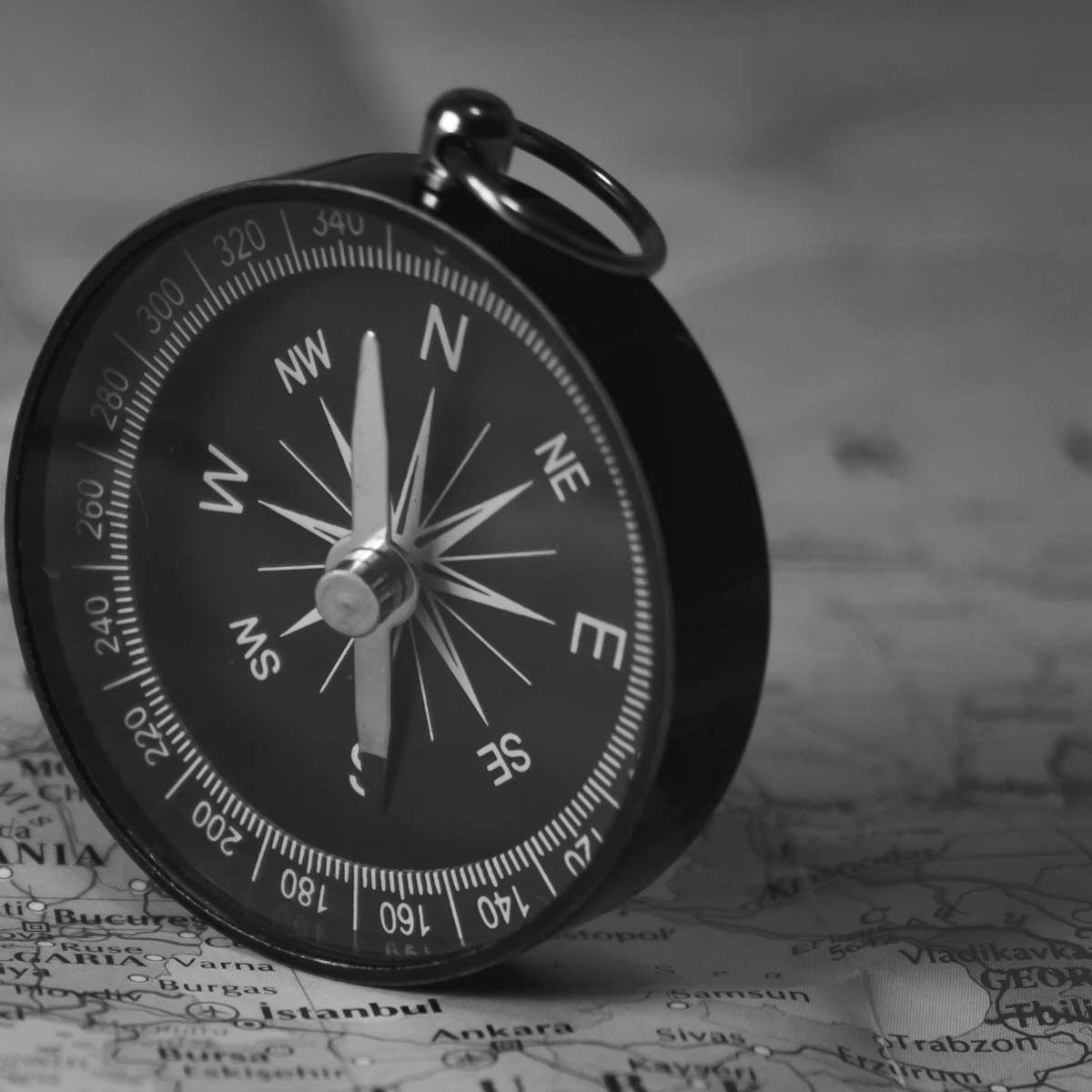 compass on a black and white tourist map. Focus on the compass needle