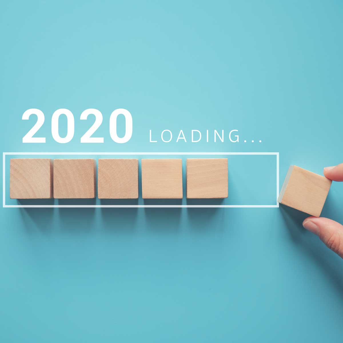 Loading new year 2020 with hand putting wood cube in progress bar.