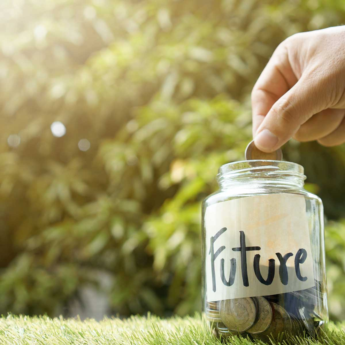 Money saving, Hand putting coin in glass jar with coins inside For now and future money. Concept of saving money for future.