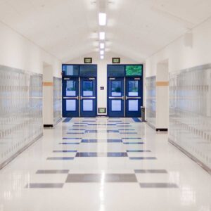 School Hallway with lockers on walls and blue doors to outside