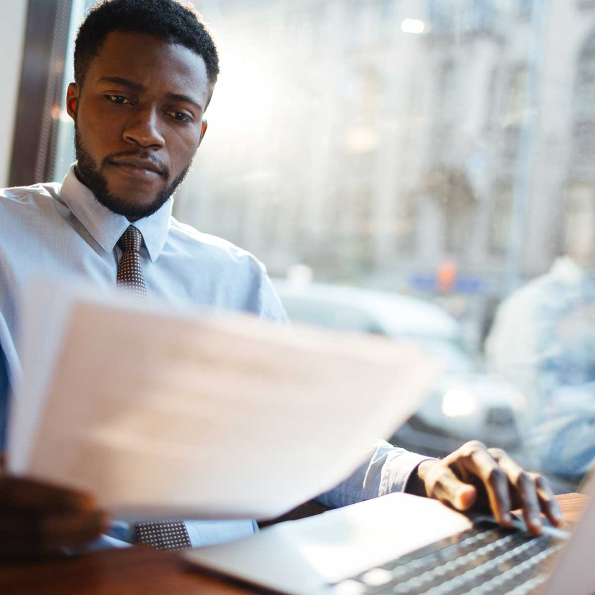 Serious employer reading paperwork with laptop on desk