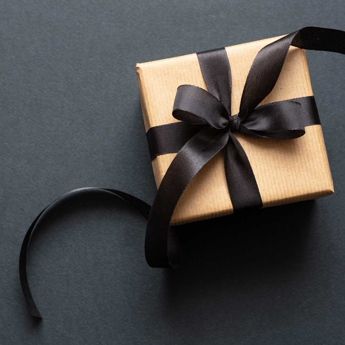 Gift box with black ribbon against black background